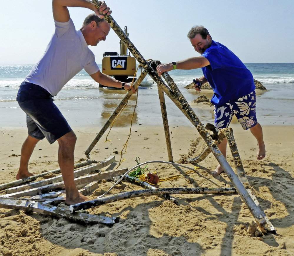 Peter Brockmann, left, president of the East Beach Association, gets help assembling pieces of a mystery object removed from the surf Thursday.