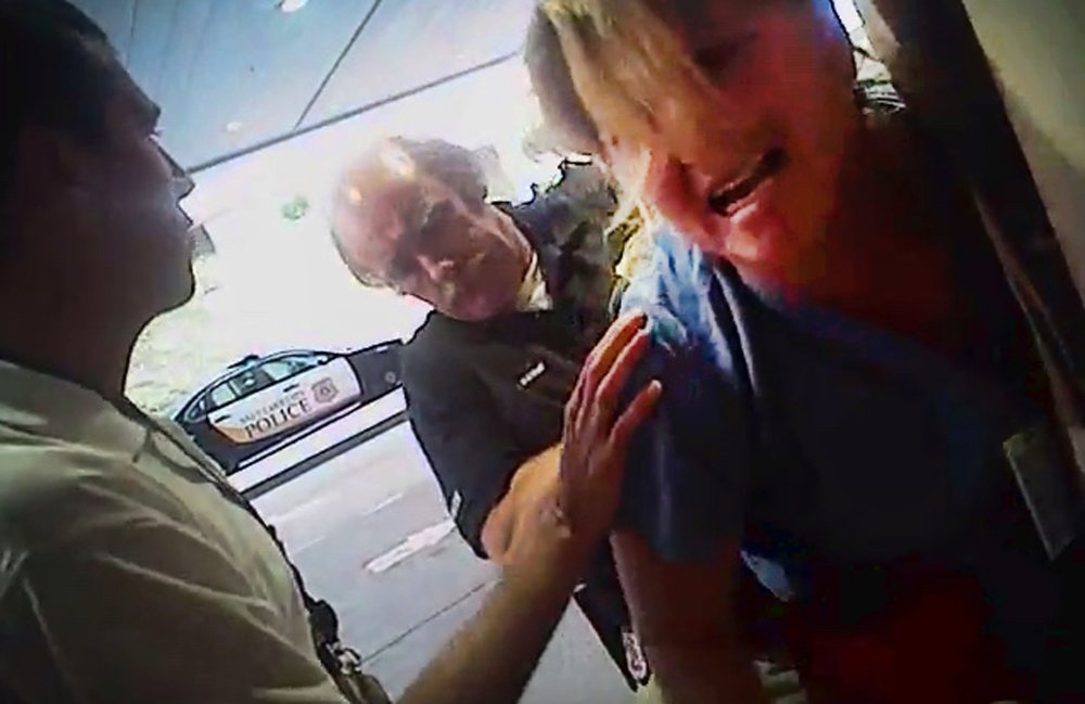 In this July 26 frame grab from a police body camera, nurse Alex Wubbels is handcuffed by a Salt Lake City police officer at University Hospital in Salt Lake City. Above, Wubbels, right, looks on during an interview with her attorney.