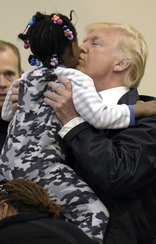 President Trump lifts a little girl and gives her a kiss as he and Melania Trump meet people impacted by Hurricane Harvey during a visit to the shelter at the NRG Center in Houston, Texas, on Saturday.