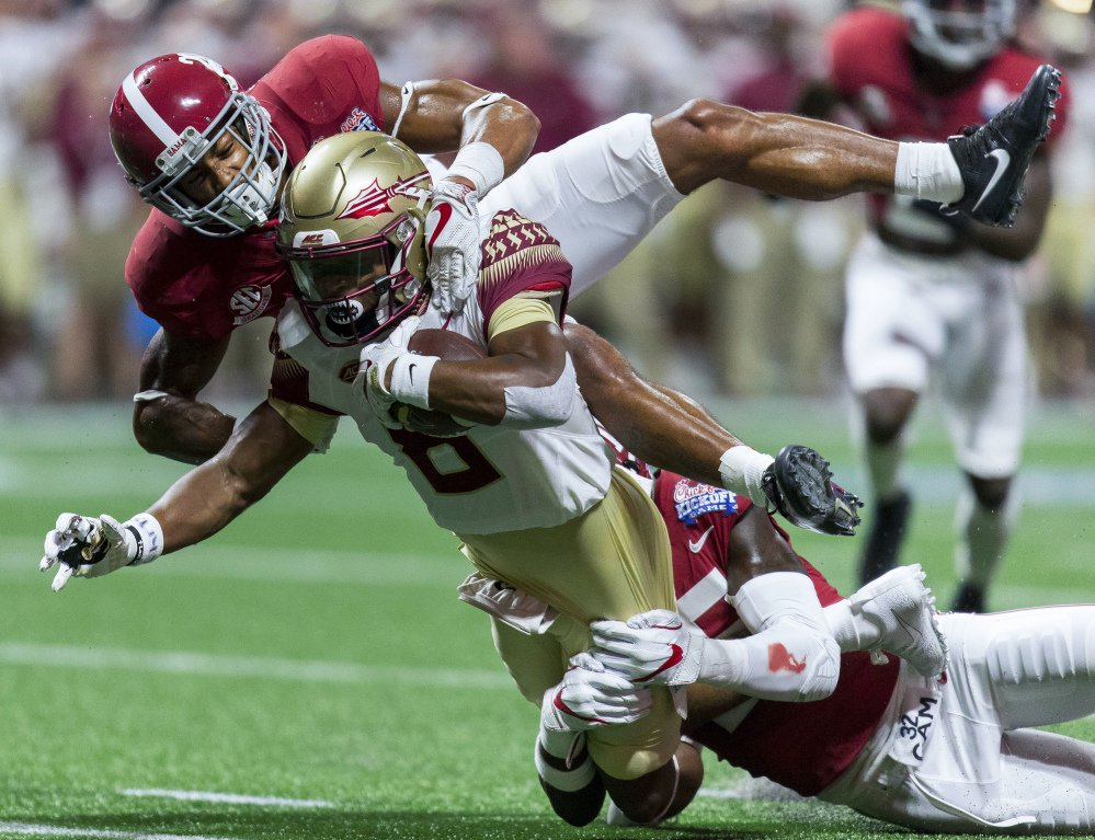 Alabama defensive backs Anthony Averett, top, and Shyheim Carter (5) stop Florida State wide receiver Nyqwan Murray.