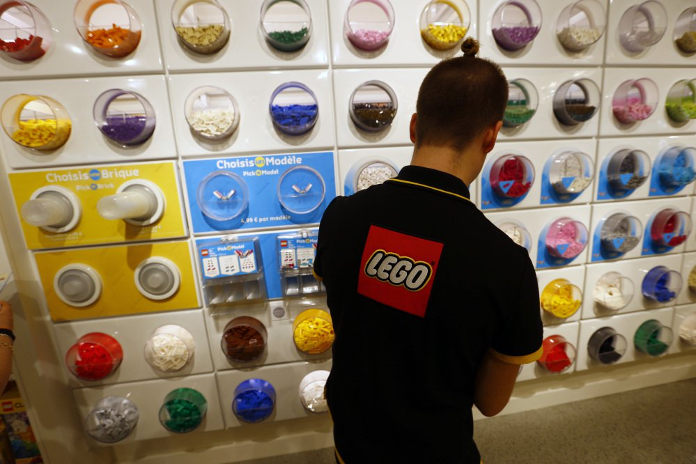 A worker sorts Legos in a Paris store. The company's revenue dropped 5 percent in the first half of this year, to $2.4 billion, with weaker demand in the U.S. and Europe.