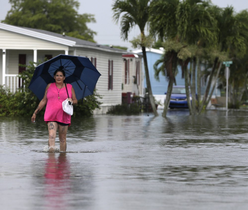 Peggy Wallace walks near her flooded neighborhood in Davie, Fla., in June. As Hurricane Irma bears down on Florida, an AP analysis shows that the number of federal flood insurance policies written in the state has fallen by 15 percent.