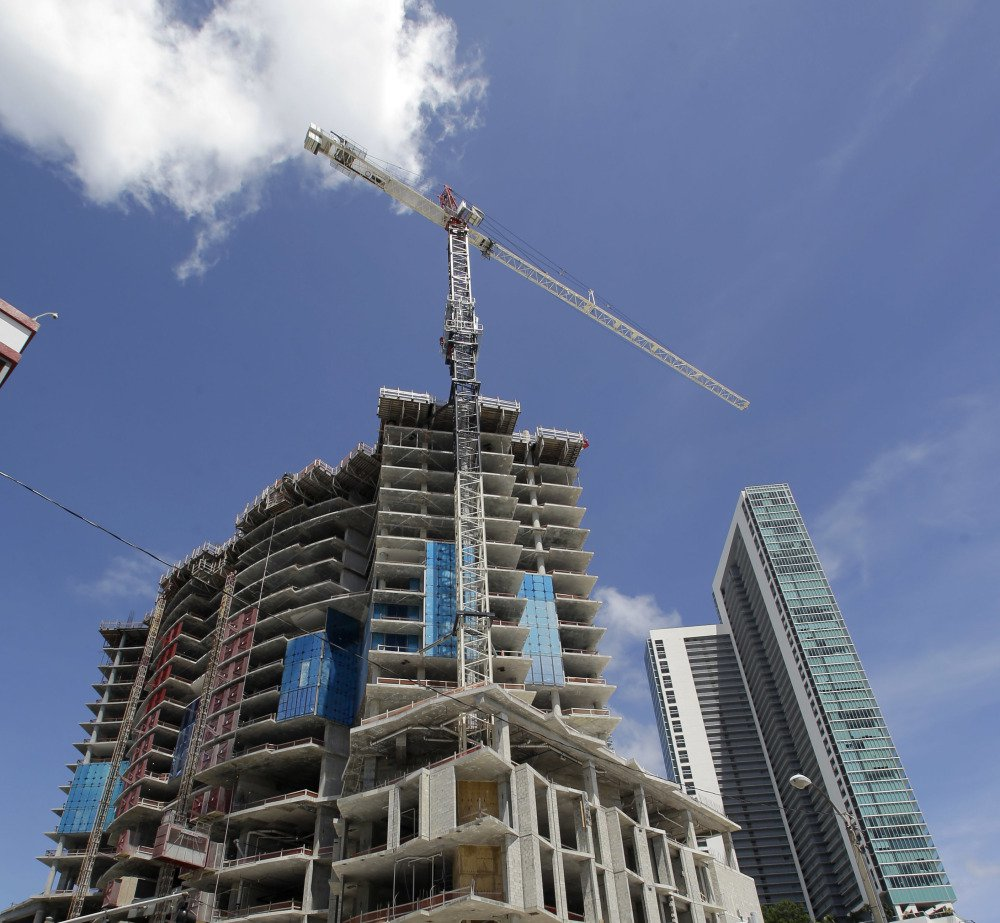 A crane on a building under construction may damage the high-rise at right during a hurricane, even though the cranes are designed to spin like weather vanes.