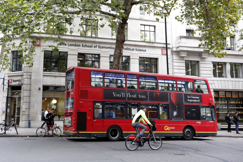 A double-decker bus pulls up to London School of Economics in London.