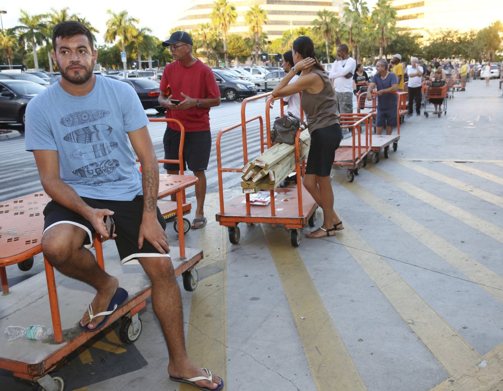 "In this Sept. 6, 2017 file photo, Max Garcia of Miami, waits in line to purchase plywood sheets at a Home Depot store in North Miami, Fla. With images of Hurricane Harvey's wrath in Texas still fresh and 25-year-old memories of Hurricane Andrew's destruction, warnings that Hurricane Irma might be the long-dreaded ""big one"" has brought many Floridians close to panic. Lines for gas, food and supplies stretched outside businesses as the South Florida region of more than 6 million people rushed to prepare for Irma, which forecasters say could strike over the weekend as a Category 4 or 5 storm. (AP Photo/Marta Lavandier, File)"