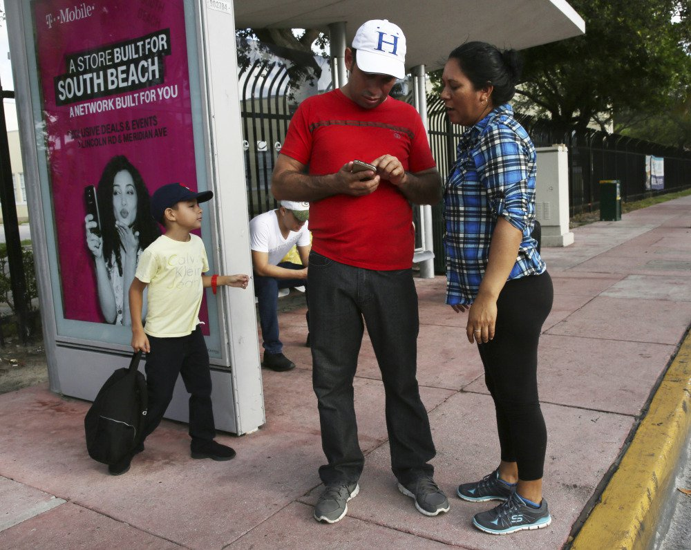 Wilman Hernandez and his wife, Brenda Ramirez, check their phones for the location of shelters and their capacity while waiting for a bus in Miami Beach, Fla. Meanwhile, the main hub leading Floridians out of Hurricane Irma's path is bumper to bumper with those who can afford to escape.