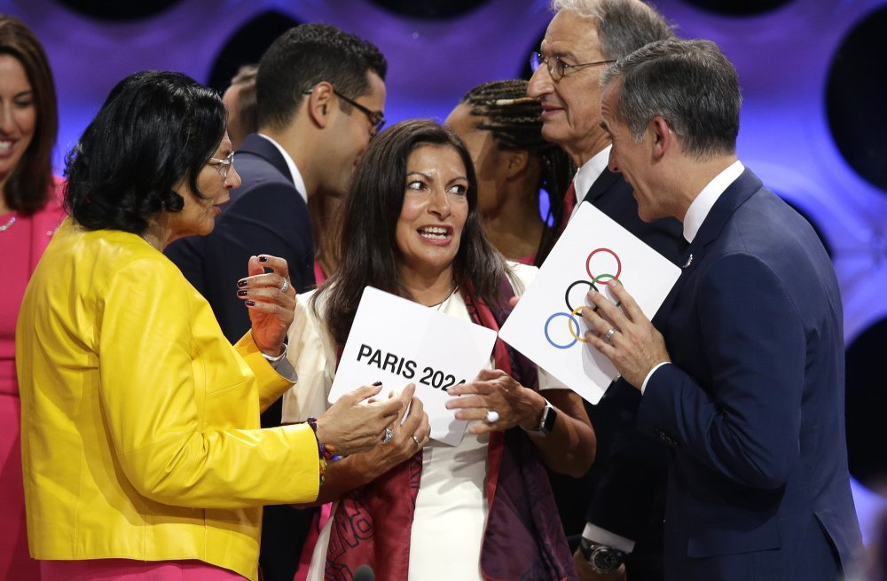 Paris Mayor Anne Hidalgo, center, speaks with Los Angeles Mayor Eric Garrett, right, and Los Angeles International Olympic Committee member Anita DeFrantz, left, in Lima, Peru on Wednesday where Los Angeles (2028) and Paris (2024) were named to play host for the Summer Olympic games.