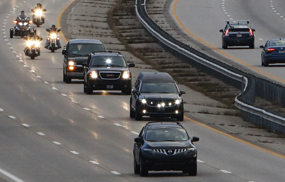 A hearse carrying the body of Marine Capt. Ben Cross is escorted by Maine State Police and Patriot Guard Riders as it travels north on Route 95 in Kittery Thursday evening on its way to Bethel, where Cross spent his childhood.