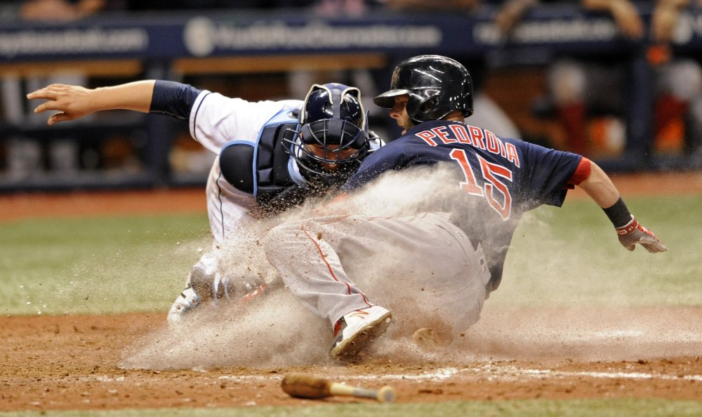 Boston's Dustin Pedroia slides by the tag from Tampa Bay catcher Jesus Sucre to score on Keith Moreland's RBI single during the 15th inning early Saturday morning in St. Petersburg, Fla. The Red Sox won 13-6 to stay three games up in the AL East.