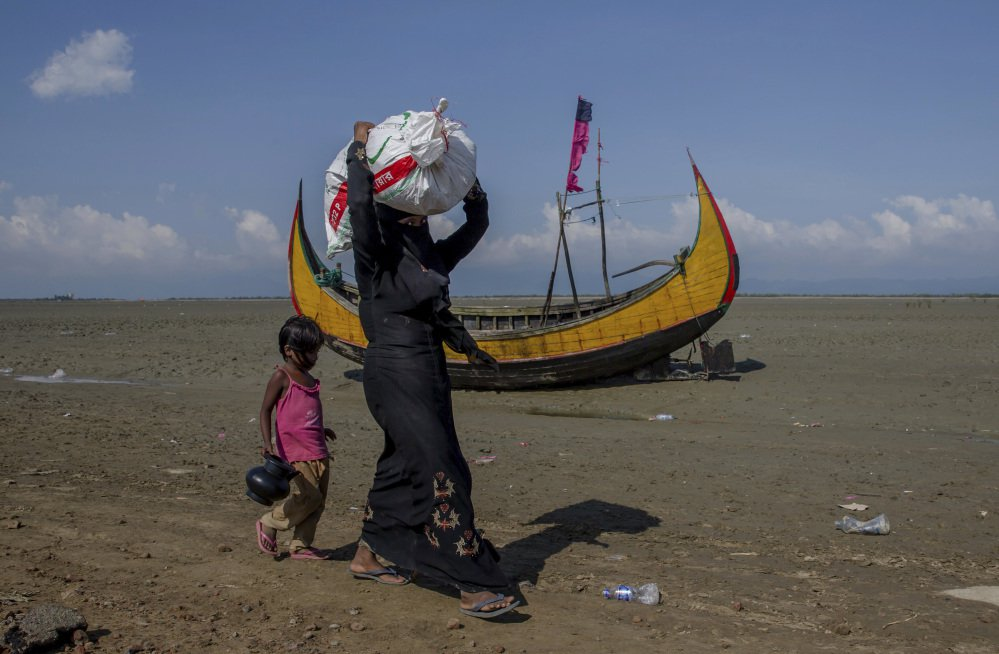A Rohingya Muslim woman, who crossed over from Myanmar into Bangladesh, walks with her daughter after receiving aid in Teknaf, Bangladesh, on Saturday. United Nations agencies say about 409,000 Rohingya Muslims have fled to Bangladesh since Aug. 25.