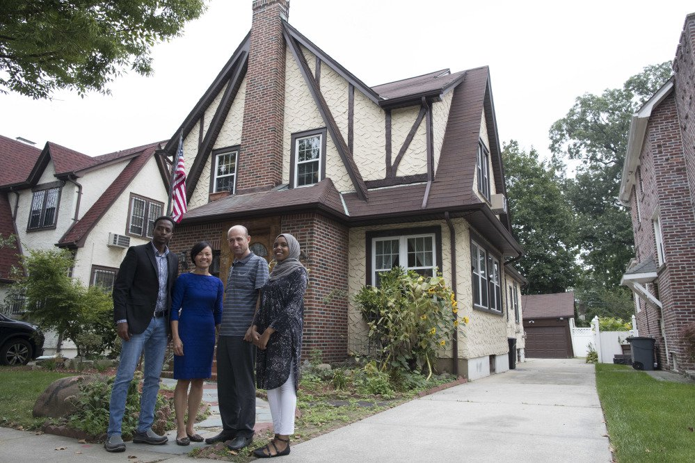 Abdi Iftin, left, of Somalia, Uyen Nguyen, second from left, of Vietnam, Eiman Ali, right, of Somalia born in Yemen, and Ghassan al-Chahada, of Syria pose for a photo outside President Trump's boyhood home in the Jamaica Estates neighborhood of the Queens borough of New York.