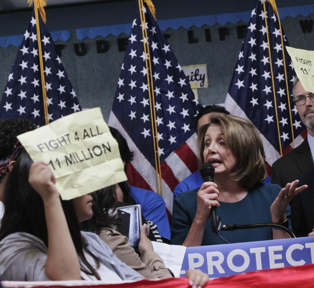 House Minority Leader Nancy Pelosi tries to talk as protesters demonstrate during a press conference on the immigration on Monday in San Francisco, Calif.