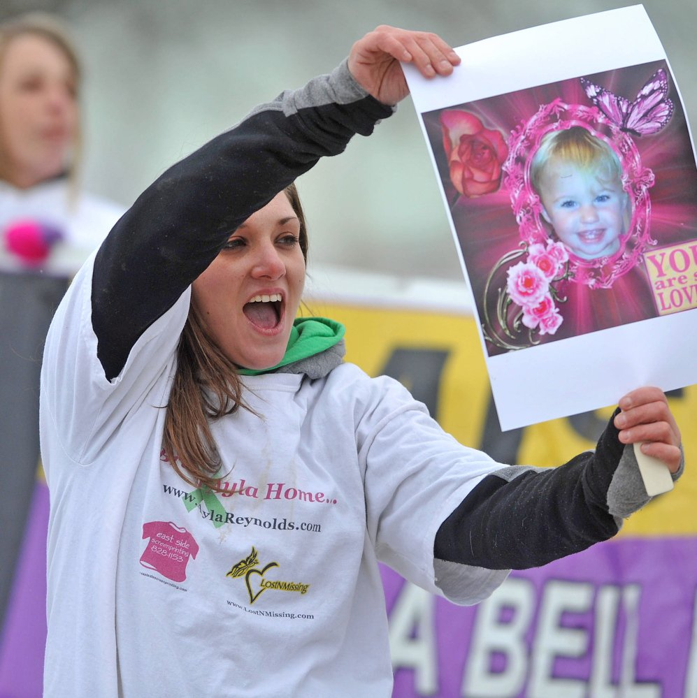 Trista Reynolds, mother of missing toddler Ayla Reynolds, holds a picture of her daughter at the Colby Circle College Avenue intersection in Waterville.