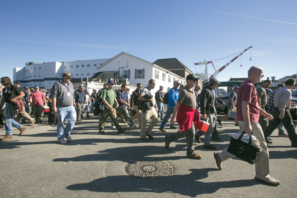 Workers leave the main gate after first shift ends at Bath Iron Works last September.