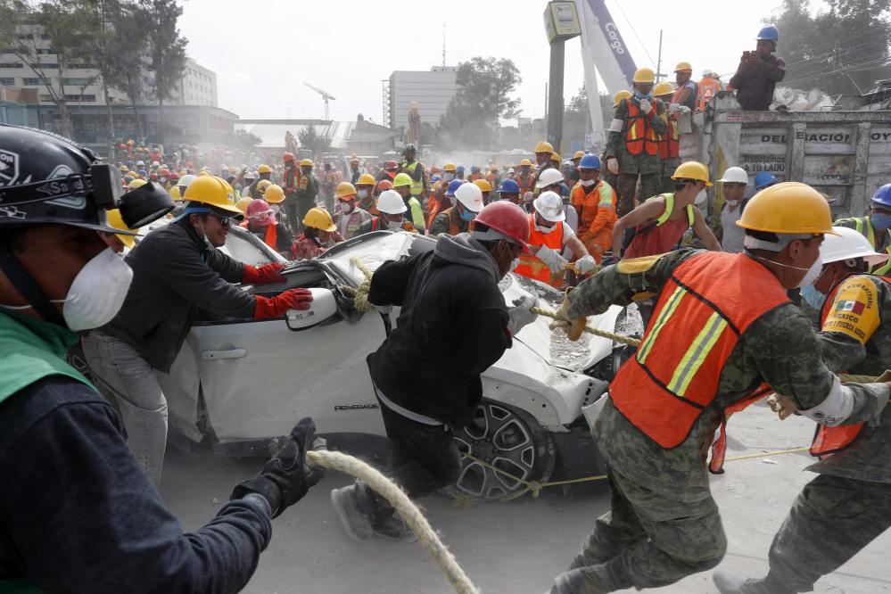Volunteers and soldiers remove a destroyed vehicle from the parking lot of a four-story clothing factory in Mexico City that was brought down by Tuesday's 7.1-magnitude earthquake.