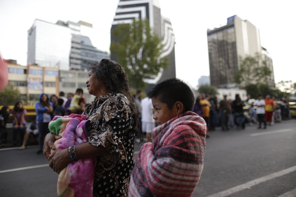 People stand in the street after hearing an earthquake alarm in Mexico City on Saturday. A strong aftershock rolled through Mexico City on Saturday morning, swaying buildings and sending some people running into the street.