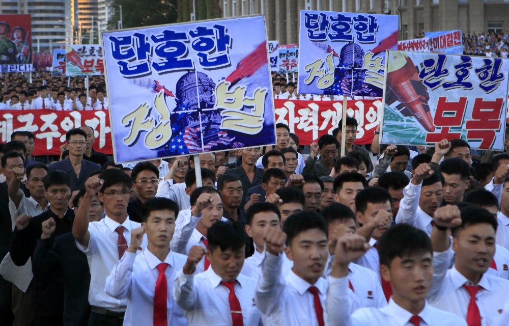 "North Koreans gather in Kim Il Sung Square to attend a mass rally against America on Saturday in Pyongyang, North Korea, a day after the country's leader issued a statement attacking President Trump. The sign in the left foreground reads ""decisive punishment."""