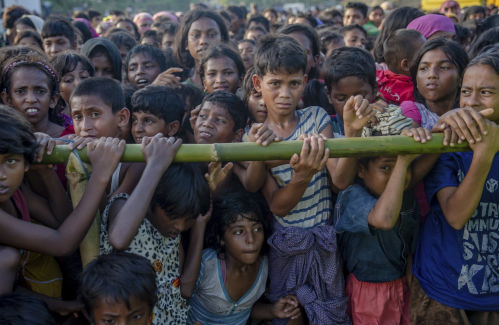 Rohingya Muslim children who entered Bangladesh to escape violence in Myanmar wait to receive aid Monday during a distribution near the Balukhali refugee camp.