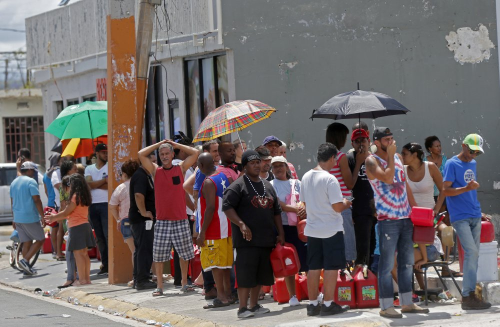 In the aftermath of Hurricane Maria, residents of San Juan, Puerto Rico, line up to get fuel from a gas station on Monday. The U.S. ramped up aid amid criticism that it wasn't doing enough.