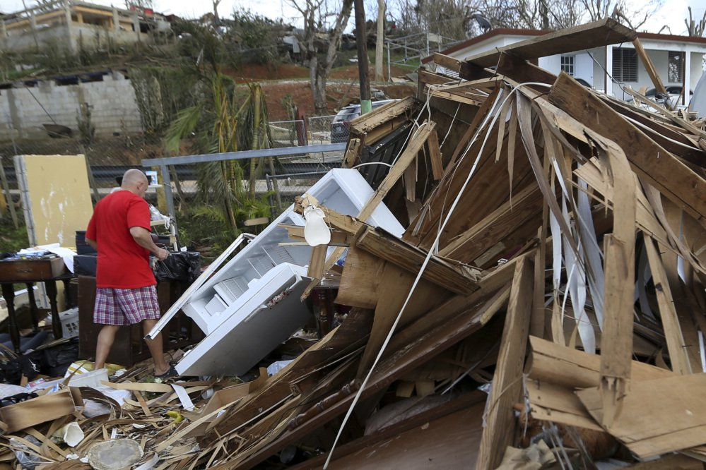 A man walks through the rubble of his destroyed home in Aibonito, Puerto Rico, Monday. Damaged airports and seaports have made it challenging to get help to the island.