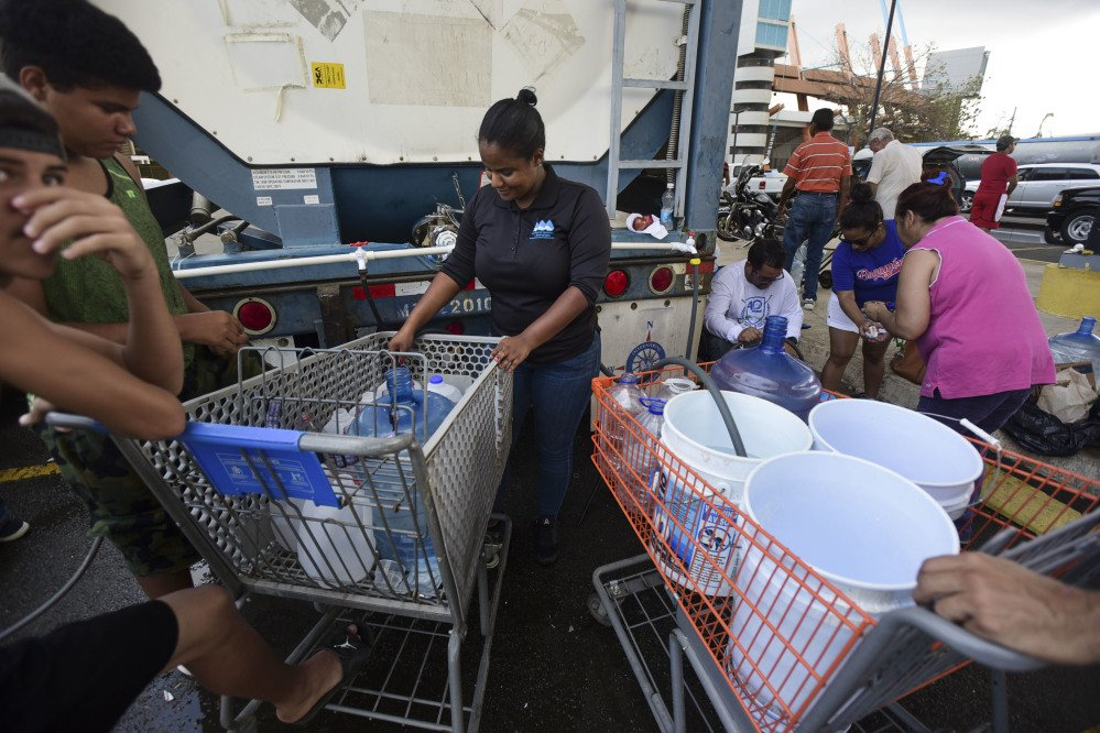 A municipal government worker fills containers with drinking water Thursday for residents outside the Juan Ramon Loubriel stadium in in Bayamon, Puerto Rico. Many people fear that it will get even harder to survive on the storm-ravaged island.