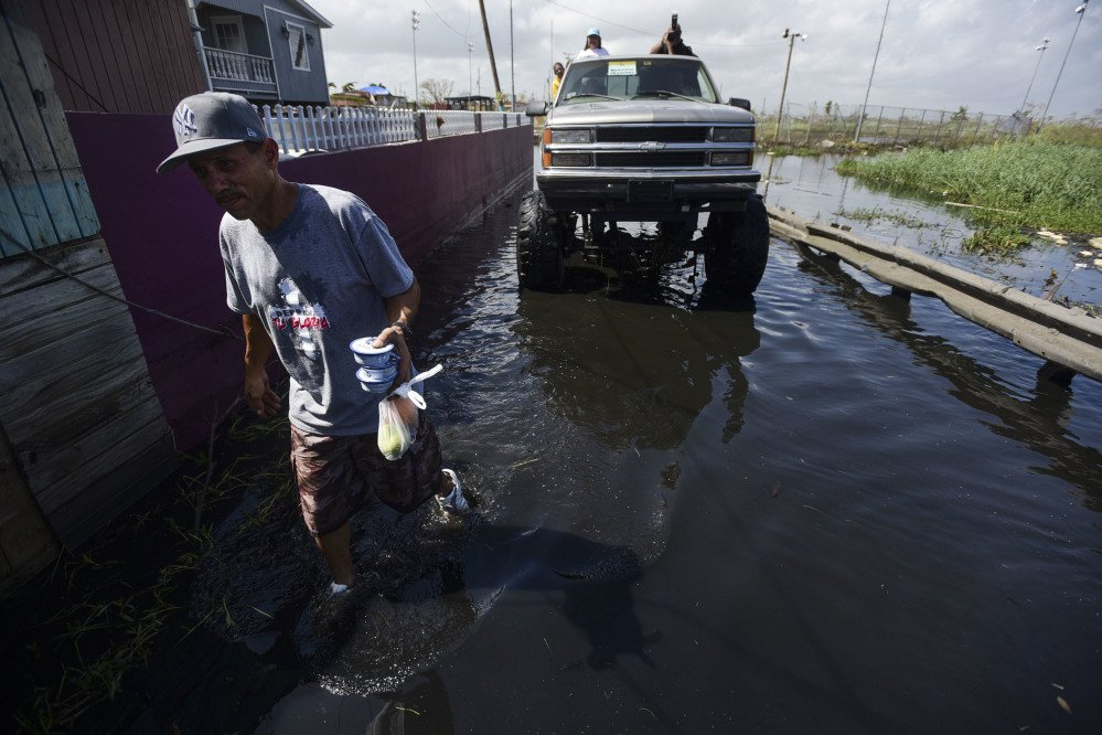 Amado Hernandez walks through a flooded area in Catano, Puerto Rico, on Thursday, carrying fruit and canned food one week after the passage of Hurricane Maria. The powerful storm has caused a near-total shutdown of the U.S. territory's economy that could last for weeks.