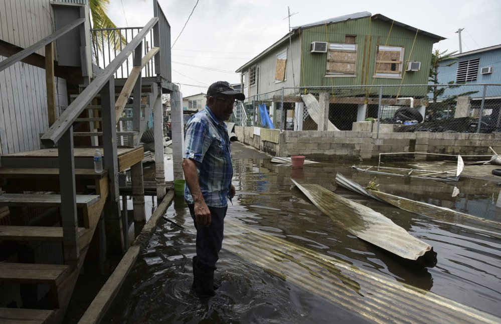 Hector Rosa walks through a flooded area of Juana Matos, Puerto Rico, on Wednesday. At left, Christian Mendoza counts money in the aisle of a San Juan supermarket, where he had hoped to buy bottled water but found only cans of juice Monday. Widespread communication failures have complicated relief efforts on the island territory of 3.4 million people.
