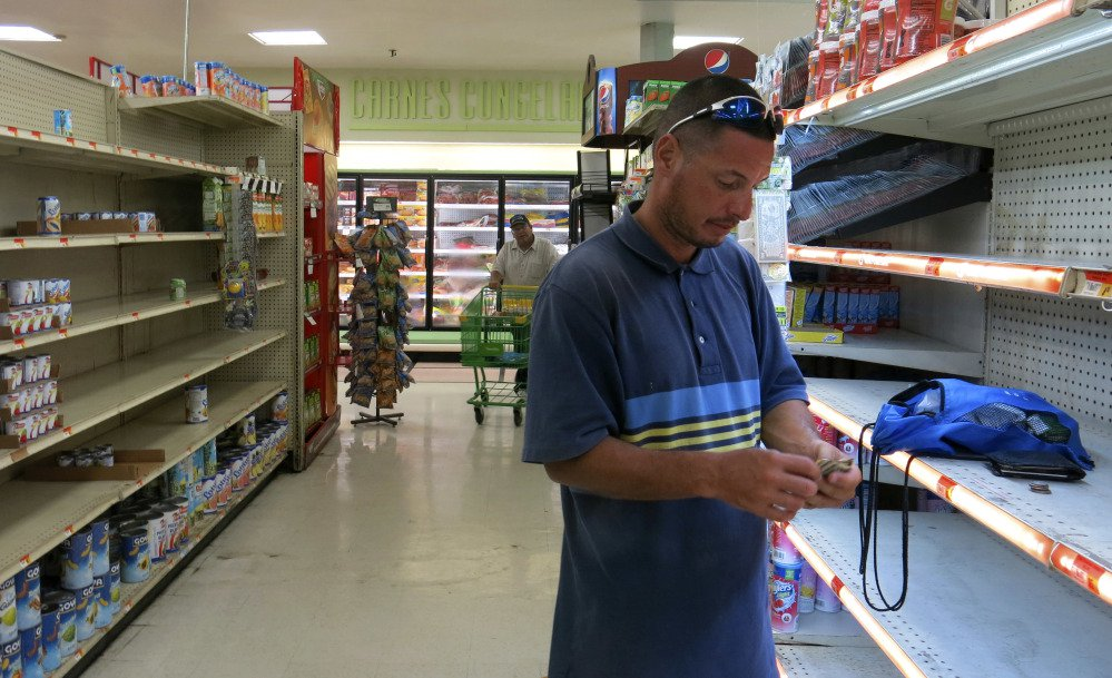 In this Monday, Sept. 25, 2017 photo, Christian Mendoza counts money in the aisle of a supermarket where he had hoped to buy bottled water but only found cans of juice, in San Juan, Puerto Rico. Mendoza said the car wash where he works hasn't re-opened so he has been selling bottled water, even though he isn't able to refrigerate it. (AP Photo/Ben Fox)