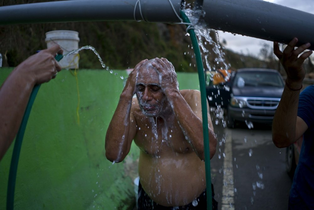 Residents bathe in water piped from a creek in Naranjito, Puerto Rico, on Thursday. Even before the hurricane, the island's recession led hundreds of thousands to flee to the U.S. mainland.