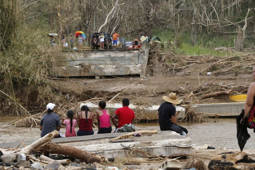 People sit Wednesday on both sides of a destroyed bridge that crossed the San Lorenzo de Morovis River in Morovis, Puerto Rico. Maria has thrown Puerto Rico's already messy economic recovery plans into disarray.