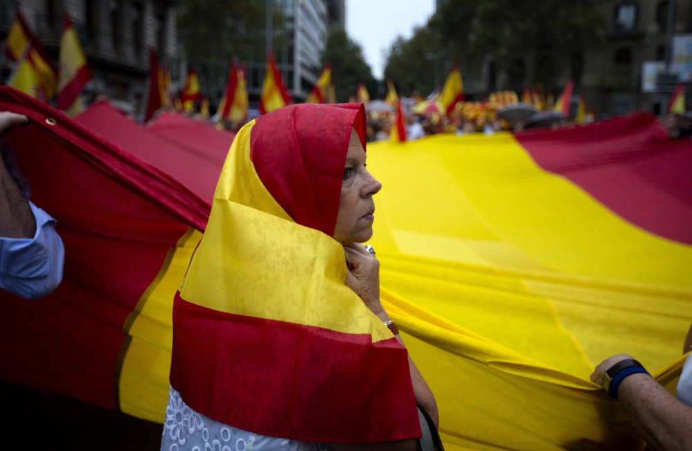 Anti-independence demonstrators waving Spanish flags march against the referendum by the pro-independence Catalan government in downtown Barcelona on Saturday.