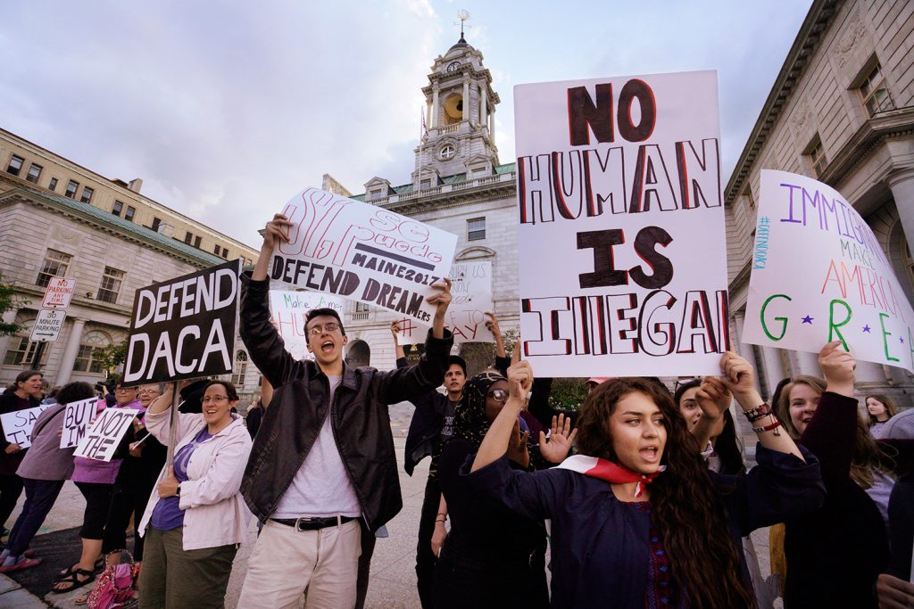 "Kathleen Armenta, holding a sign saying ""No human is illegal,"" chants ""D-A-C-A, Dreamers have the right to stay"" with other people at Portland City Hall on Friday evening. Armenta is a freshman at Bowdoin College from Tucson, Arizona. She says her parents came to the United States from Mexico while she was in her mother's womb."