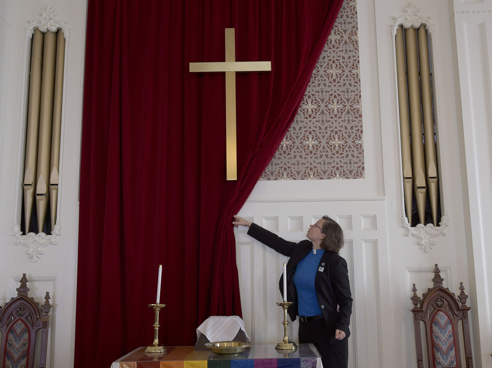 The Rev. Chrissy Cataldo exposes artwork Wednesday in the chapel of the Winthrop Congregational Church, which is raising funds to repair the building.