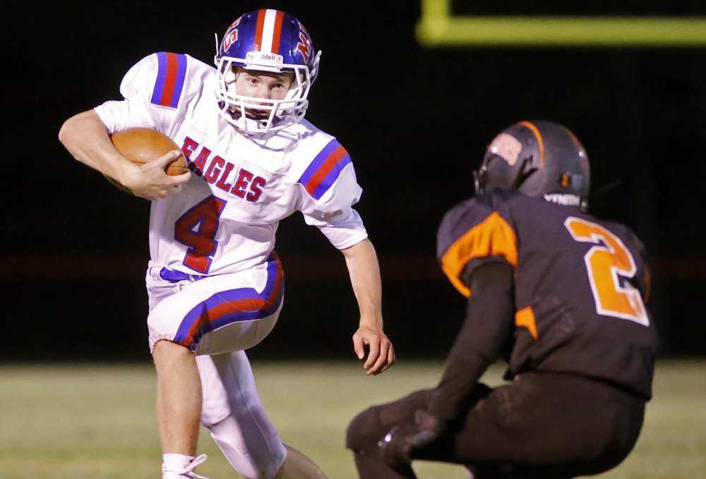 Messalonskee quarterback Deklan Thurston tries to out-maneuver Brunswick defensive back Dalton Dickey during a Pine Tree Conference B game Friday in Brunswick.