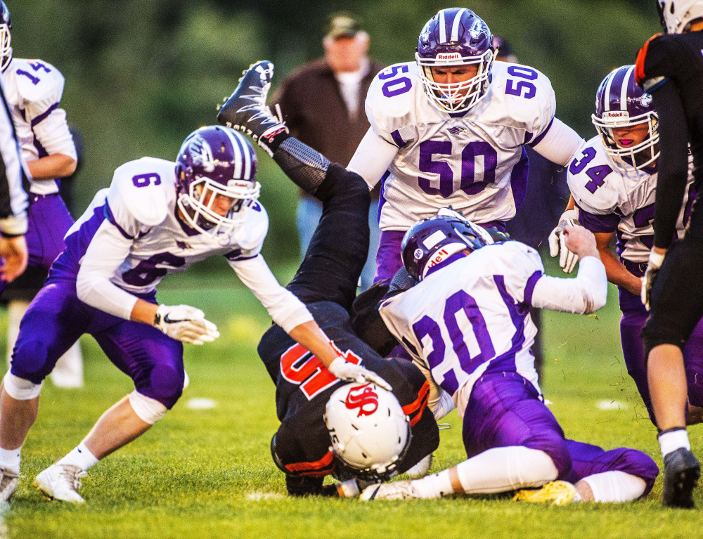 Skowhegan running back Hunter Washburn gets up-ended by Marshwood junior Dylan Strong (20) during a Class B game Friday night at Clark Field in Skowhegan.