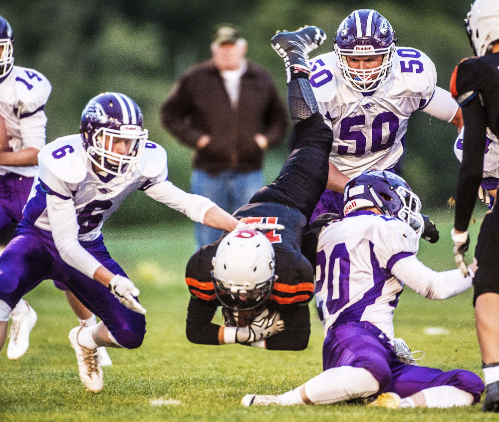 Skowhegan running back Hunter Washburn takes a tumble to the Clark Field grass as a host of Marshwood defenders converge for the tackle during a Class B game Friday night at Clark Field in Skowhegan.