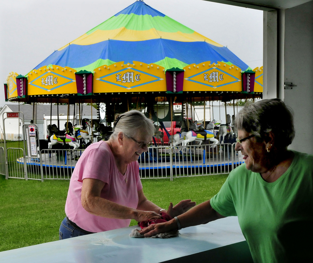 Pam Nuite, left, and Shirley Pierce, of the Clinton Evening Extension organization, clean off counter space Tuesday at the club's dough-boy kiosk for the upcoming 2017 Clinton Lions Agricultural Fair. The fair runs Thursday though Sunday.