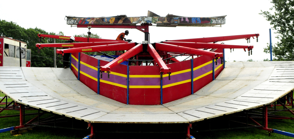 A carnival worker erects the Music Fest ride Tuesday for the upcoming 2017 Clinton Lions Agricultural Fair. The fair runs Thursday though Sunday.