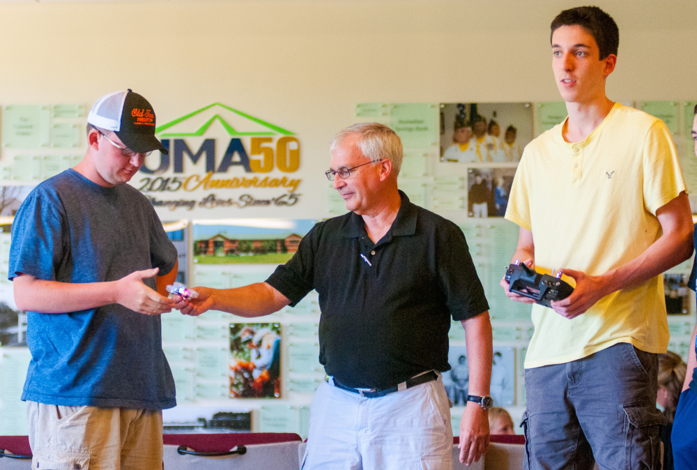 Lewiston High School student T.J. Morin, left, takes a small drone from aviation instructor Dan Leclair as fellow Lewiston High student waits with his hands on the remote control to try flying it July 28 in Randall Hall on the University of Maine at Augusta campus.