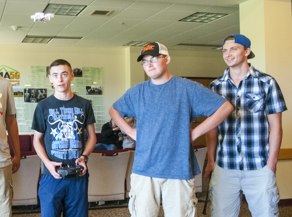 Lewiston High School student Noah Bisson, left, flies a small drone July 28 in Randall Hall on the University of Maine at Augusta campus. T.J. Morin, center, from Lewiston High, and Curtis Ouellette, of Edward Little High School, watch.