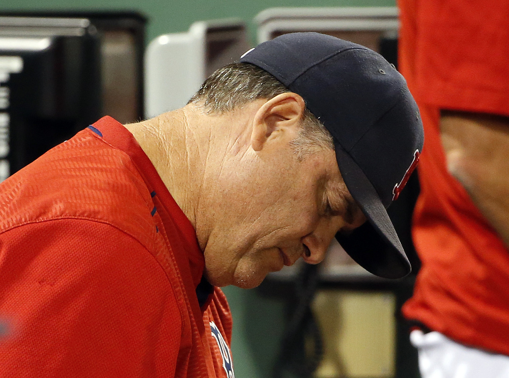 Boston Red Sox manager John Farrell takes notes in the dugout during the eighth inning of a game against the Blue Jays on Monday.