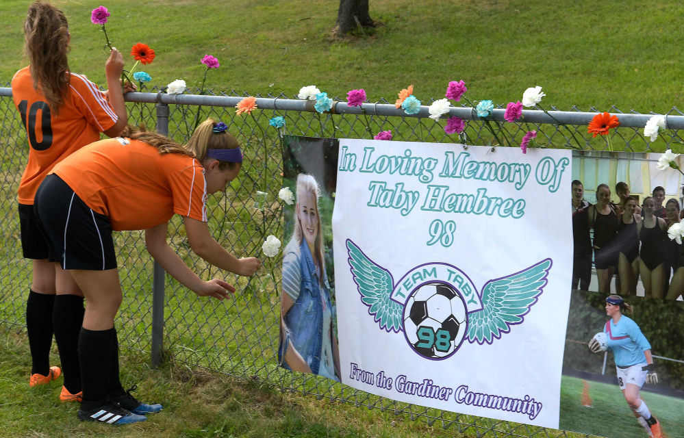 Gardiner Area High School soccer players adorn a fence with flowers in memory of teammate Tabytha Hembree, who died in a car accident last Thursday, prior to a game Tuesday against Leavitt in Gardiner.