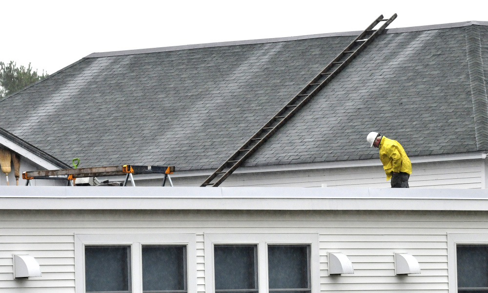 A worker surveys the roof of China Middle School after roots penetrated older drain pipes causing Tuesday evening's rain water to back up Wednesday.
