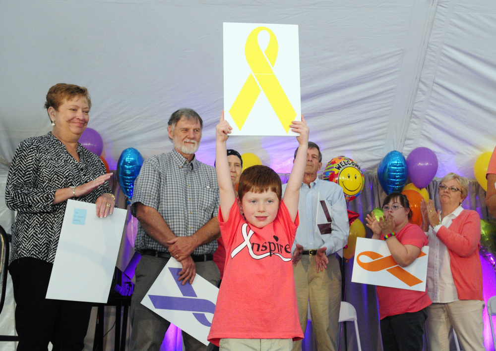 Nathan Wade holds up a yellow ribbon, symbol of Ewing's sarcoma, for which he was treated for at the Harold Alfond Center for Cancer Care, during the center's 10th anniversary celebration on Saturday in Augusta.