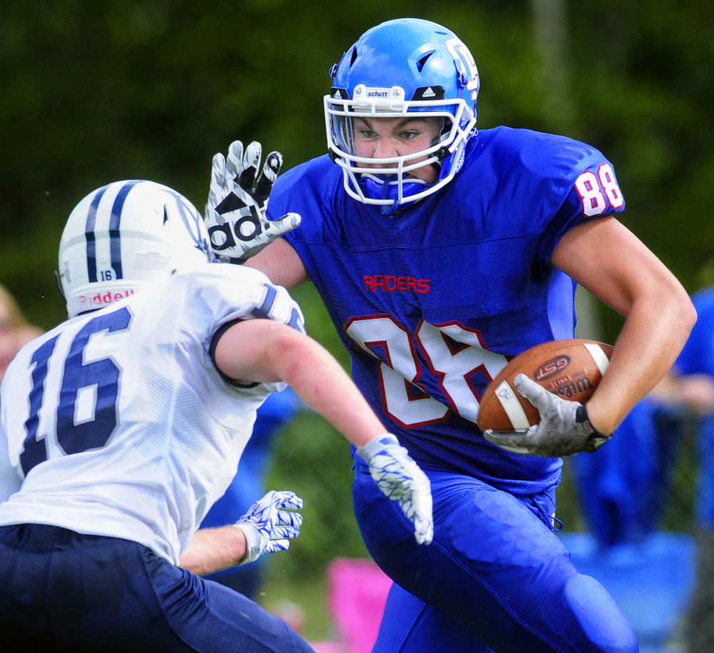 Oak Hill's Austin Pierce reaches out to ward off Yarmouth linebacker Ben Gleason on Saturday afternoon in Wales.