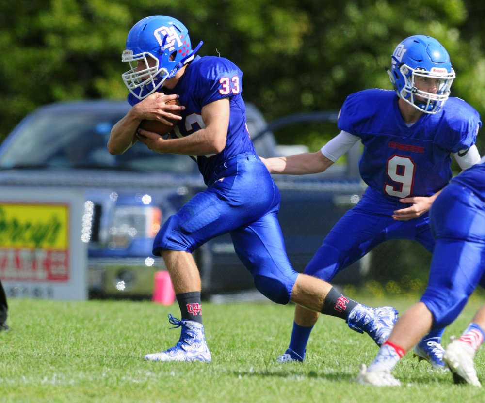 Oak Hill running back Cruz Poirier (33) takes a handoff from quarterback Gavin Rawstron during Saturday's game against Yarmouth in Wales.