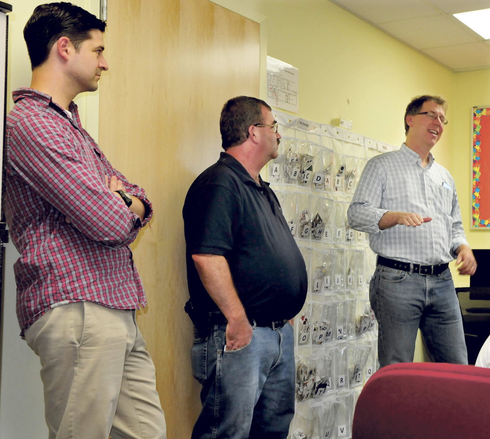 Kevin Mattson, right, discusses the 59-unit apartment housing project in the former Seton Hospital building in Waterville on Sunday. Listening is Mayor Nick Isgro, left, and Councilor Sydney Mayhew.