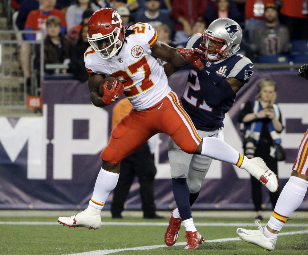 Kansas City Chiefs running back Kareem Hunt (27) eludes New England Patriots cornerback Malcolm Butler as he crosses the goal line for a touchdown Thursday.