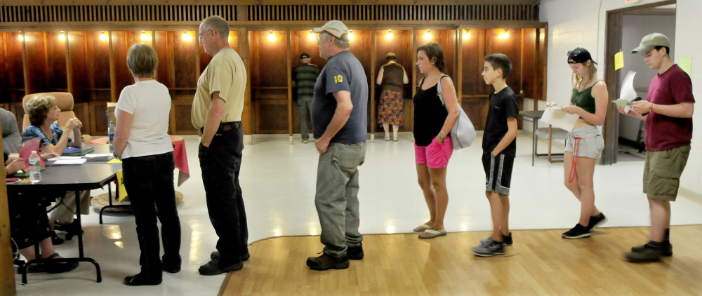 Voters cast their ballots Tuesday in voting booths as other Farmington residents wait in line to obtain ballots for the Regional School Unit 9 school budget vote at the Community Center in Farmington.