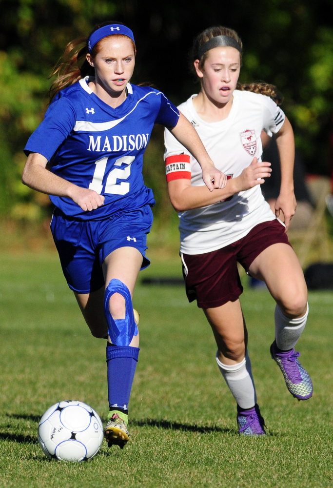 Madison forward Ashley Emery, left, chases a loose ball with Monmouth's Emily Grandahl during a Mountain Valley Conference game against Monmouth last season.